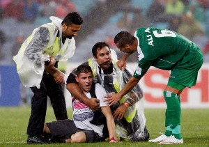 Iraq's Ali Adnan Kadhim speaks to security personnel detaining a pitch invader during their Asian Cup semi-final soccer match against South Korea at the Stadium Australia in Sydney J